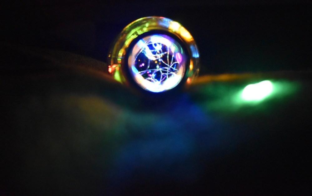 Blick in eine Flasche mit einer Lichterkette beleuchtet im Dunkeln