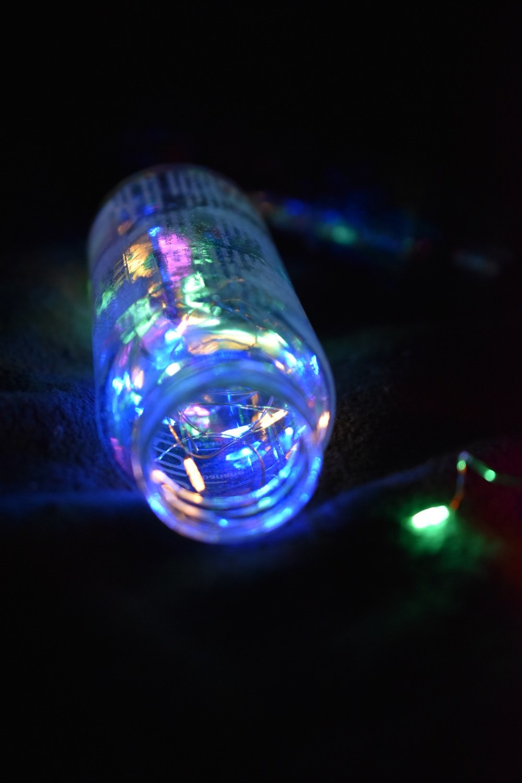 Leuchtende kleine Glasflasche im Dunkeln
