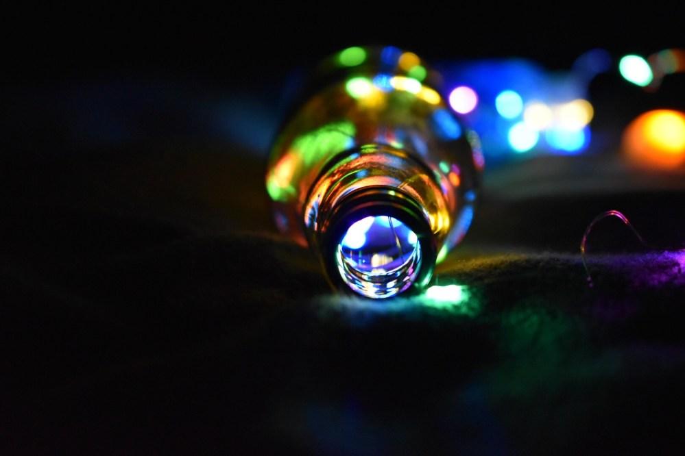 Bunt leuchtende Glasflasche mit Lichterkette