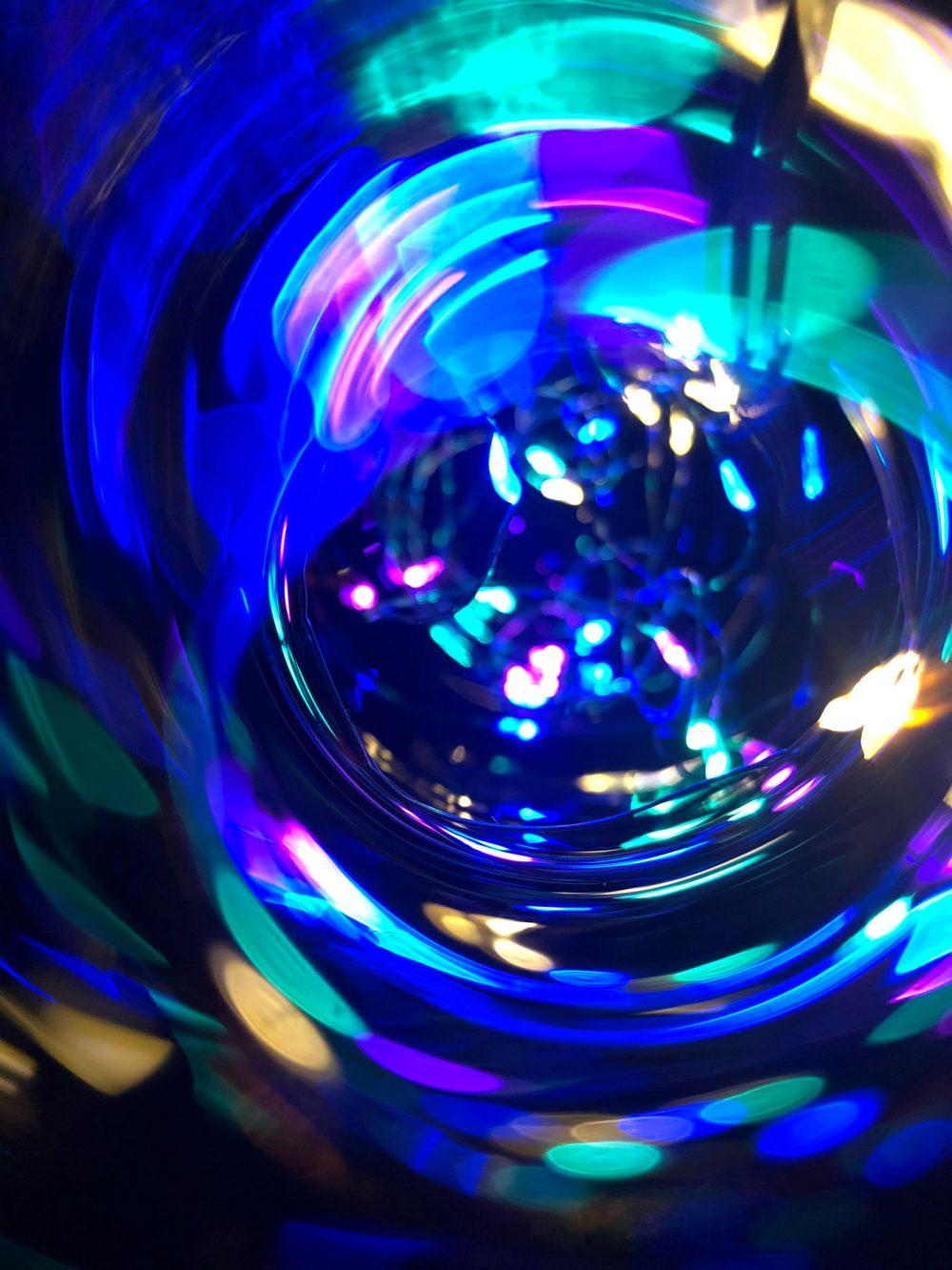Viele bunte Lichtflecken kreisen in der Flasche herum