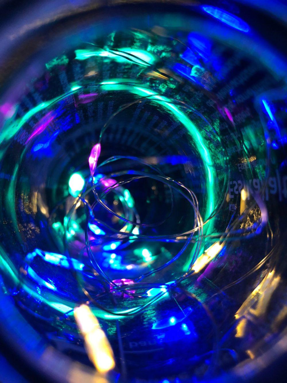 Türkisfarbene und pinkfarbene Licht erstrahlen die Flasche im Dunkeln
