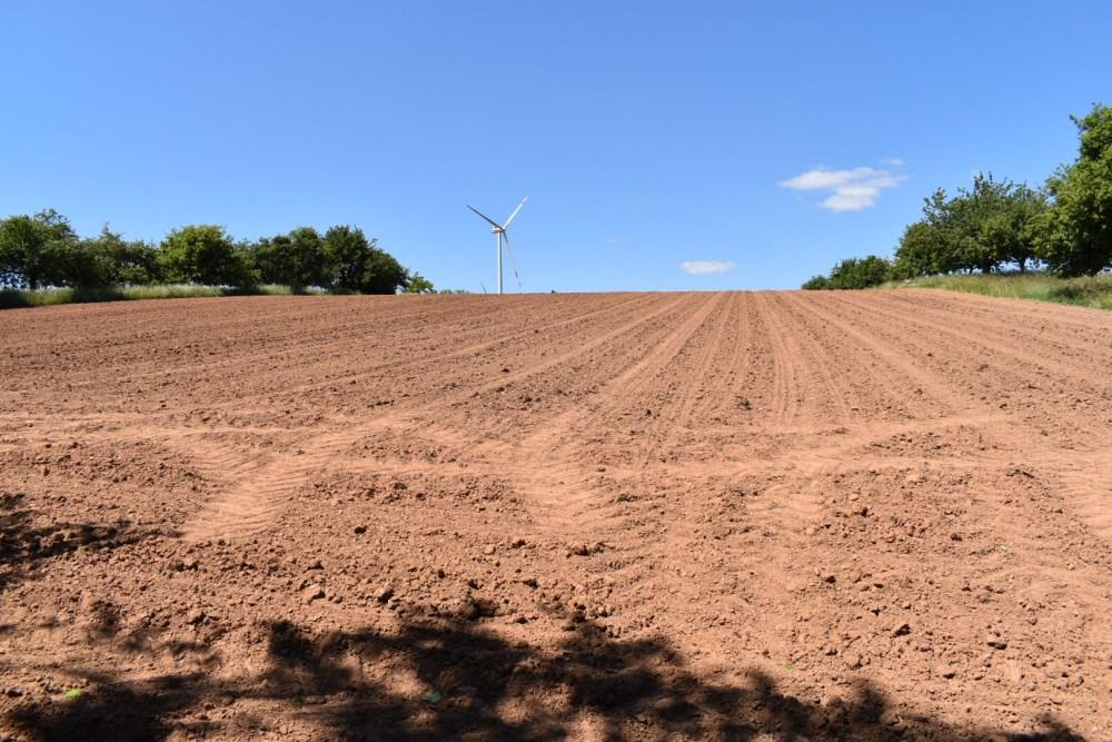 Ackerfläche mit Windrad im Hintergrund