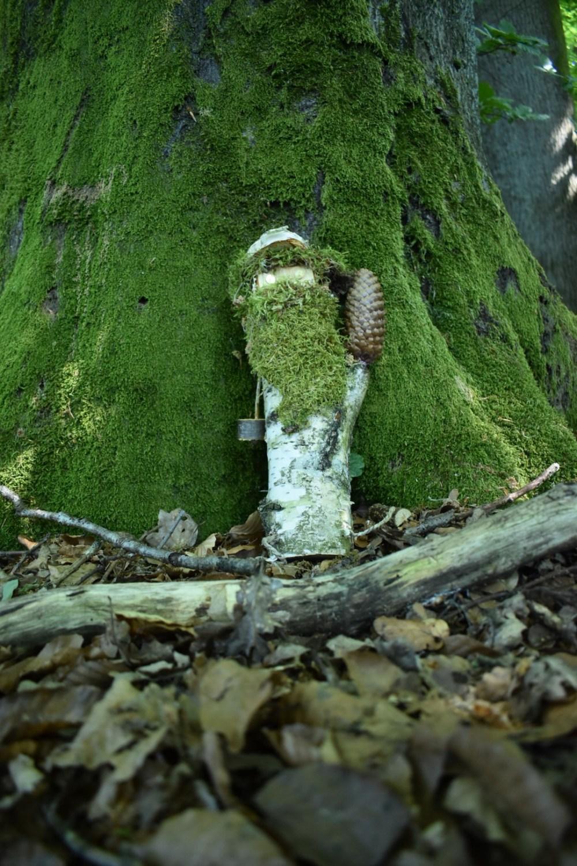 Niedliche Holzfigur mit Moosbart im Wald