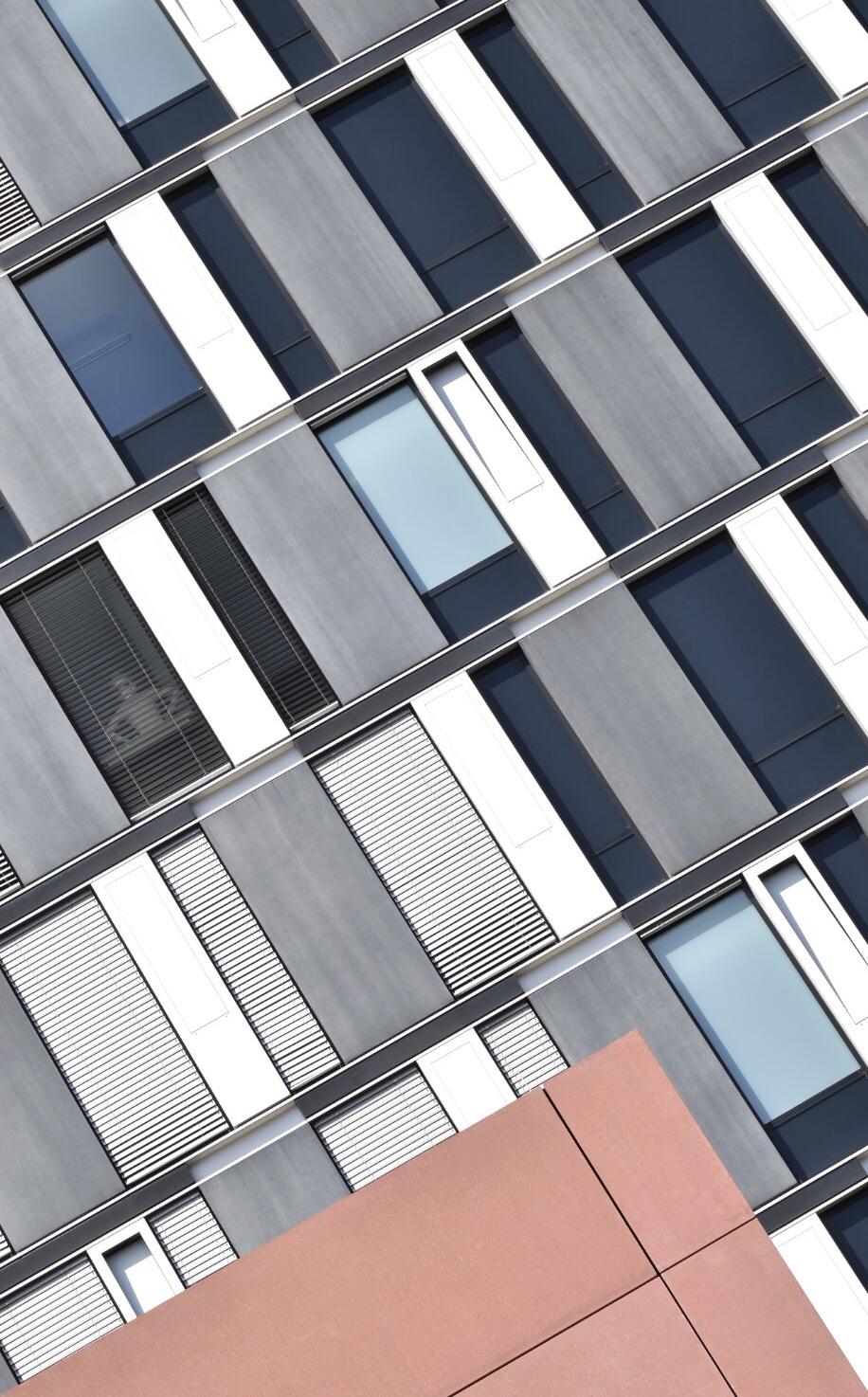 Rötliches Gebäude vor der Fensterfassade eines Hochhauses