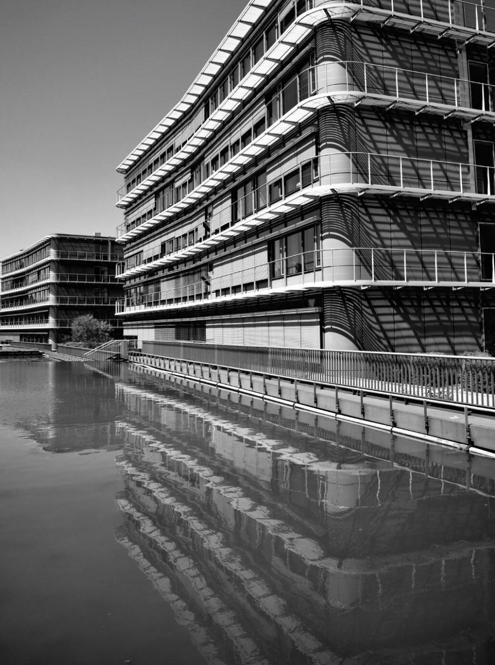 Bürogebäude spiegelt sich im Wasser (schwarz weiß bearbeitet)