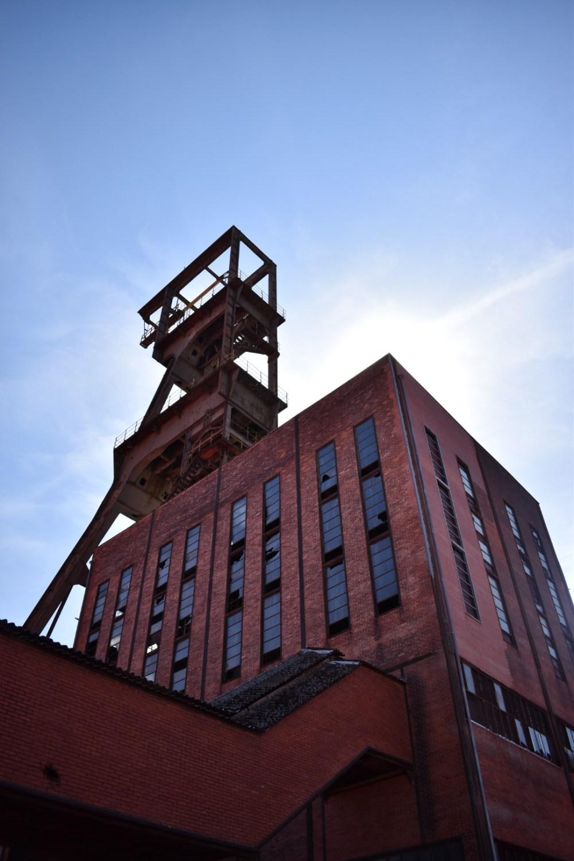 Rotes Gebäude mit zerstörten Fenstern von unten fotografiert