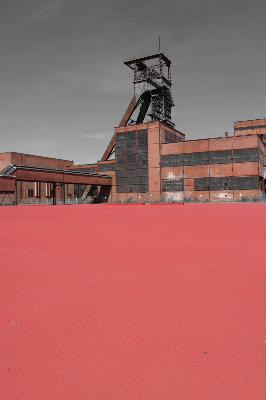 Rotes Gelände des Bergwerks mit Förderturm im Hintergrund