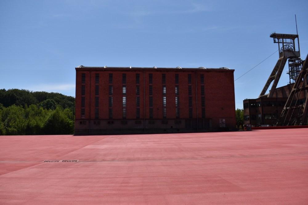 Rotes Haus hinter der roten Fläche des Parc Explor Wendel