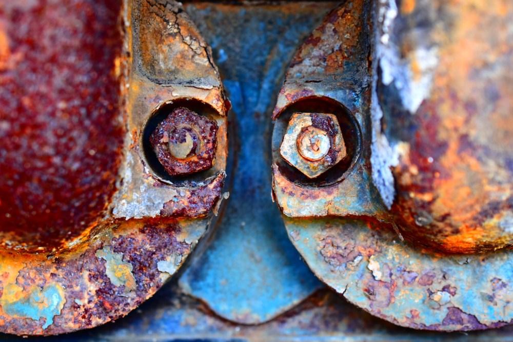 Verrostete Schrauben an zwei Rohren, mit stark gesättigter Farbe fotografiert
