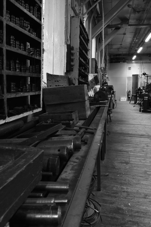 Tische mit altem Zeug aus der Fabrik in schwarz weiß fotografiert