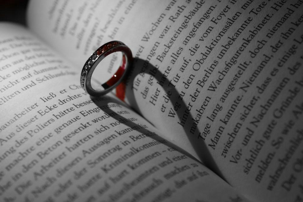 Blutiger Ring mit Herzschatten auf einem aufgeschlagenem Krimi