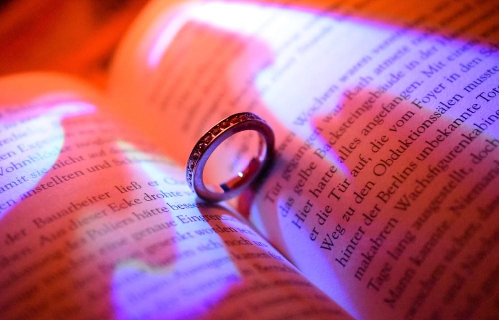 Aufgeschlagenes Buch mit Ring im orange pinkfarbenem Licht