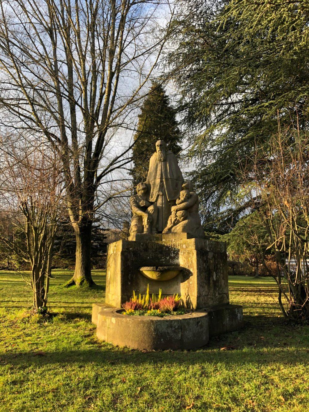 Bruder-Konrad-Brunnen mit heiligem Konrad von Parzham, kniendem Bergmann und Frau mit Kind