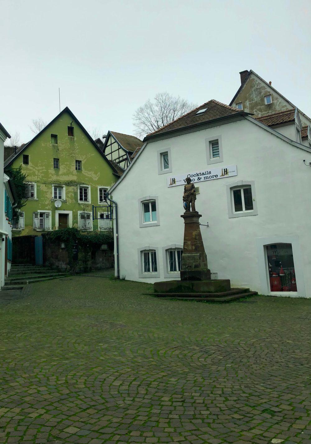 Herkulesbrunnen mit grünem Haus im Hintergrund