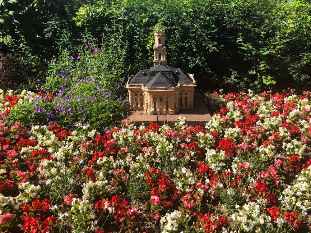 Ludwigskirche umringt von roten und weißen Blumen im Blumengarten in Bexbach