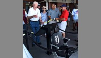 >Andy Ramotnik, a former POW, cuts the ribbon to dedicate the chair as Harold Craw, Jumbo Shrimp general manager, and Capt. Bob Buehn, USN (Ret) hold the ribbon on Monday Sept. 4, 2017, at the Baseball Grounds of Jacksonville. (Bob Mack/Florida Times-Union)