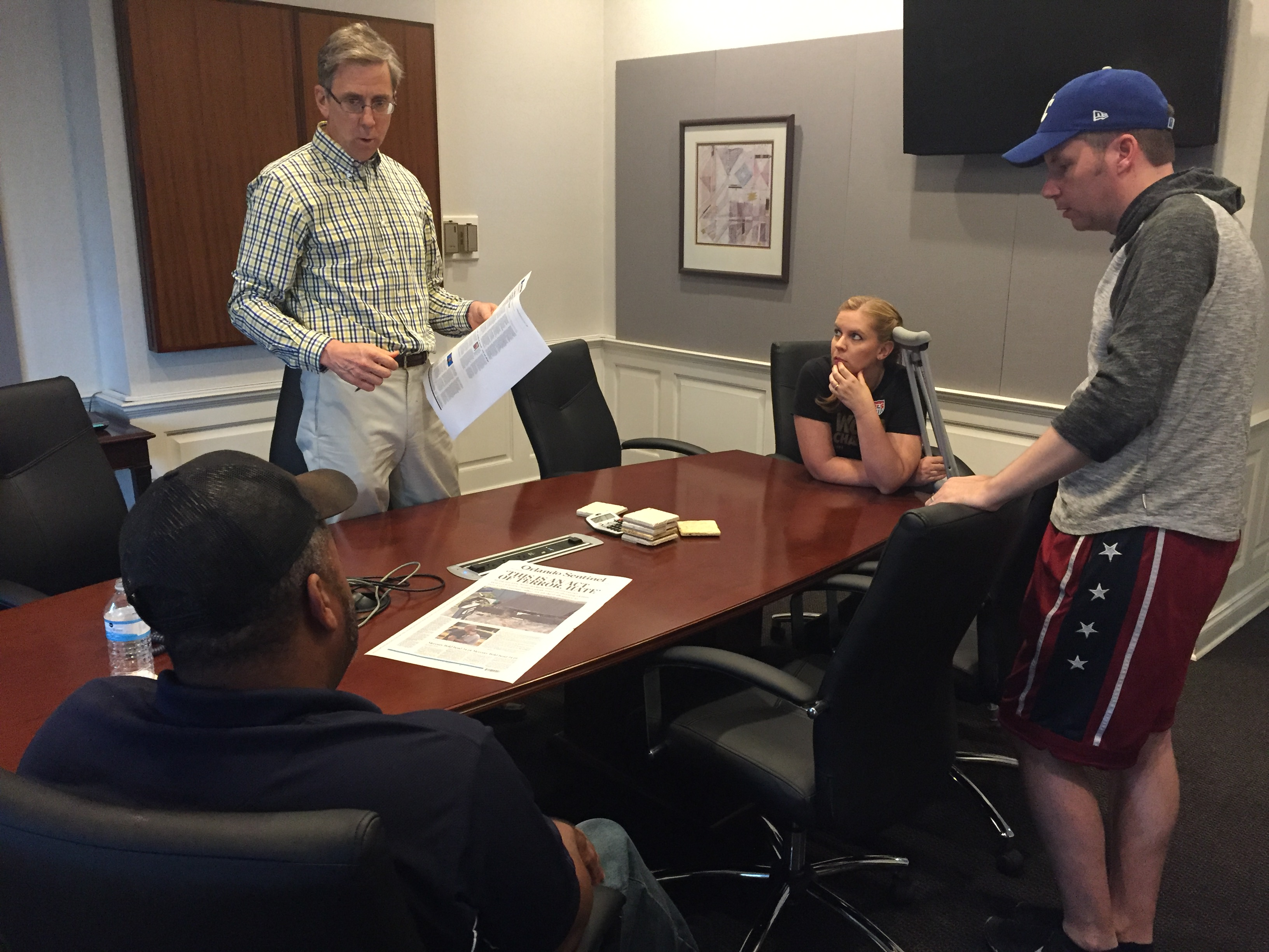 Editors discuss Monday's front page on Sunday. Pictured here, from left, are Avido Khahaifa, editor and publisher, Paul Owens, opinions editor, Cassie Armstrong, photo and video editor, and Todd Stewart, senior editor for multimedia and visuals. (Photo by Kristen Hare/Poynter)
