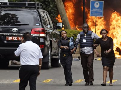 Security forces help civilians flee the scene as cars burn at a hotel complex in Nairobi, Kenya, on Tuesday, Jan. 15. Terrorists attacked an upscale hotel complex in Kenya's capital Tuesday, sending people fleeing in panic as explosions and heavy gunfire reverberated through the neighborhood. (AP Photo/Ben Curtis)