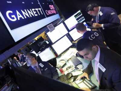 FILE - In this Aug. 5, 2014, file photo, specialist Michael Cacace, foreground right, works at the post that handles Gannett on the floor of the New York Stock Exchange. (AP Photo/Richard Drew, File)