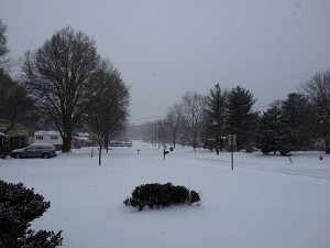 A picture of a neighborhood, looking down a street, with about a half foot of snow.
