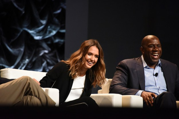 Jessica Alba and Magic Johnson sit on a stage in large white armchairs. They are seen laughing after a joke was made during the Featured Conversation discussion.