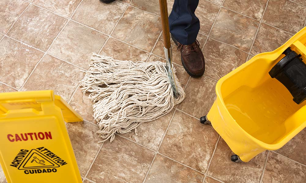 Mop being pushed on tile floor