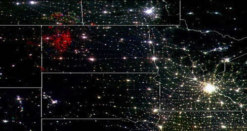 This satellite image is a composite showing nighttime lights data from the years 1992 (in blue), 2000 (in green) and 2010 (in red). White indicates lighting detected in all three years. Most of the red in the Bakken oil field area in North Dakota is due to natural gas flaring. (National Geophysical Data Center/National Oceanic and Atmospheric Administration)