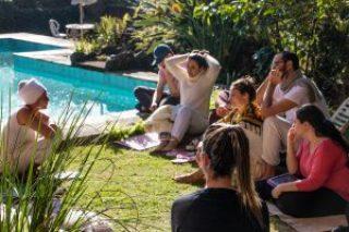 Pessoas sentadas em gramado próximo à piscina durante palestra em retiro de carnaval no Prana Prana na serra da cantareira em são paulo.