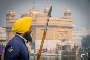 Homem em frente ao Templo Dourado em Amritsar, Índia