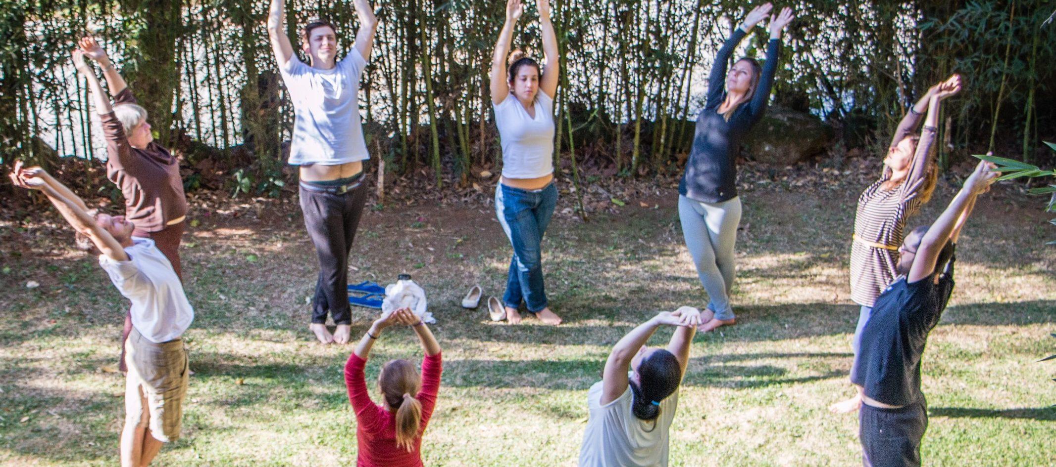 pessoas de pé formando circulo fazendo alongamento durante retiro