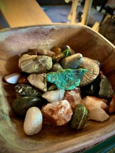 A wooden bowl filled with stones, crystals, and fossils
