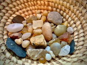 A basket filled with rocks of various sizes, shapes and colors