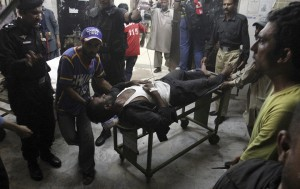 Pakistani rescue worker and police officers transport their colleague who was injured in a bomb blast at a local hospital in Karachi, Pakistan Sunday, May 24, 2015. Police say the son of Pakistan's president has escaped a roadside bomb attack unharmed after the blast killed three people and wounded 15. The attack happened late Sunday in Pakistan's restive Baluchistan province, long home to a low-intensity insurgency. (AP Photo/Fareed Khan)