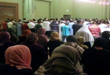 Muslim women are praying behind Muslim men.