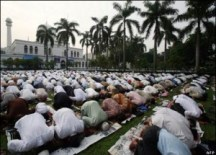 Some Muslims are performing prostration during the prayer.