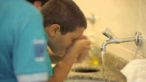 a child rinses his nose while performing ablution.