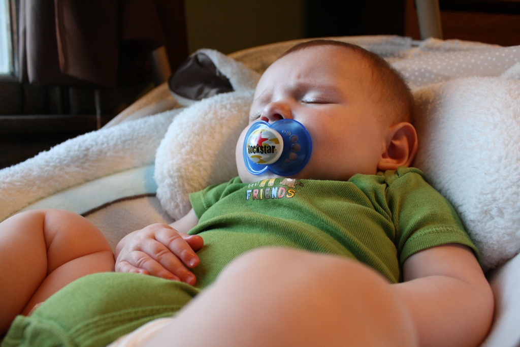 Baby Boy with Pacifier Sleeping in Swing