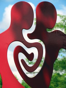 Statue of two red figures with a heart