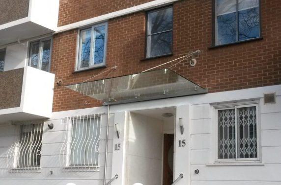 Frameless glass canopy above entrance