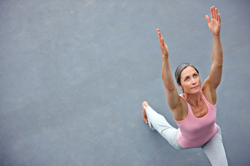 High angle shot of an attractive mature woman doing yoga outdoors