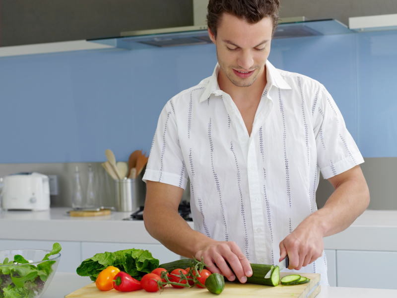 Young man cutting vegetables on wooden board in domestic kitchen