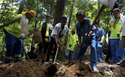 Workers exhume the remains of human trafficking victims from an abandoned mass grave in Thailand. (Reuters file)