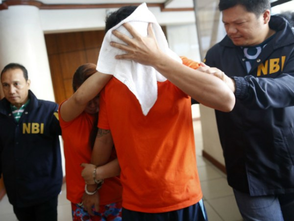 SUSPECTED TRAFFICKERS. A Filipino couple, suspected of engaging in trafficking in persons and child pornography, is escorted at the National Bureau of Investigation in Manila, Philippines, on April 26, 2016. Photo by Francis Malasig/EPA