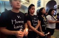 Filipino Catholics wear black shirts printed with 'Thou Shall not Kill' during a candle-lighting ceremony in Manila. (Photo by Angie de Silva)