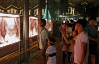 Churchgoers view photos of alleged extrajudicial killings displayed outside the Baclaran Church. (Photo by Vincent Go)