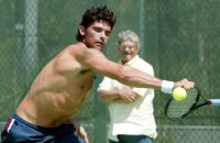 Mark Philippoussis during practise in Sydney, as his father looks on