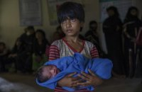 Rohingya Muslim girl Afeefa Bebi, who recently crossed over from Myanmar into Bangladesh, holds her few-hours-old brother as doctors check her mother Yasmeen Ara at a community hospital in Kutupalong refugee camp, Bangladesh, Wednesday, Sept. 13, 2017. The family crossed into Bangladesh on Sept. 3. (AP Photo/Dar Yasin)