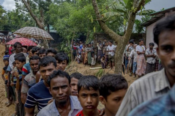 Newly arrived Rohingya wait for their turn to collect building material for their shelters distributed by aid agencies in Kutupalong refugee camp, Bangladesh, Wednesday, Sept. 13, 2017. With Rohingya refugees still flooding across the border from Myanmar, those packed into camps and makeshift settlements in Bangladesh were becoming desperate for scant basic resources as hunger and illness soared. (AP Photo/Dar Yasin)