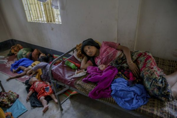 Newly arrived Rohingya women along with their children rest inside a health complex run by aid agencies in Kutupalong refugee camp, Bangladesh, Wednesday, Sept. 13, 2017. (AP Photo/Dar Yasin)