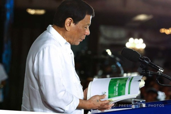FIGHTING DRUGS. President Rodrigo Duterte skims through the report of the United Nations Office on Drugs and Crime (UNODC) as he explains the effects of various illegal drugs while delivering his speech on December 5, 2017. Malacañang photo